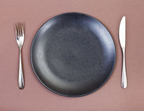 Top view of black plate, fork, knife set on brown Royalty Free Stock Image