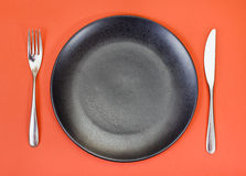 Top view of black plate, fork, knife set on red Stock Images