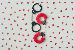 top view of black and red handcuffs with scattered paper hearts royalty free stock photography