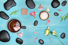 Top view of black spa stones, oil, sea salt and orchids. On blue wooden table top Stock Photography
