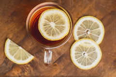 Top view of black tea with lemon in cup and on wooden plank table Royalty Free Stock Images