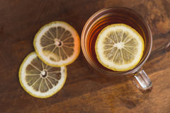 Top view of black tea with lemon in cup and on wooden plank table Stock Images