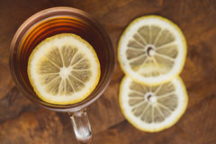 Top view of black tea with lemon in cup and on wooden plank table Royalty Free Stock Image