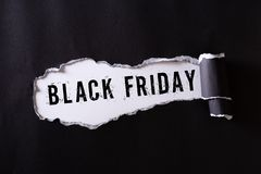 Top view of Black torn paper and the text black friday on a white background. Black Friday composition