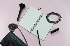 Top view of black woman bag with blank notebook, pen, cosmetics and accessories on pink background Royalty Free Stock Photos