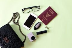 Top view of black woman bag with lipstick, earrings, small action camera, eye glasses, smart phone, passport and car key on green Stock Photos