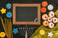 Blackboard in frame for hanukkah. Top view of blackboard in frame, menorah, donuts and cookies with star of david on wooden tabletop, hanukkah celebration Stock Photo