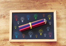 Top view of blackboard and pencils stack and various light bulbs drawing in color.  Stock Images