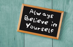 Top view of blackboard with the phrase always believe in yourself, over wooden background.  Royalty Free Stock Images