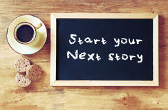 Top view of blackboard with the phrase. Start your story today next to cup of black coffee and cookies Stock Photos