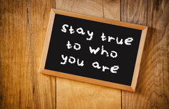 Top view of blackboard with the phrase stay true to who you are, over wooden background.  Royalty Free Stock Image