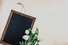 Top view of blackboard in wooden frame with eustoma flowers. On shabby background Stock Photography