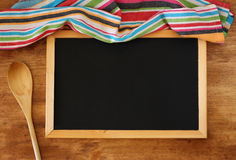 Top view of blackboard and wooden spoon over wooden table Stock Photo
