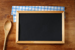 Top view of blackboard and wooden spoon over wooden table Royalty Free Stock Photography