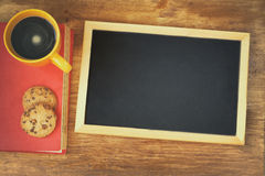 Top view of blank blackboard next to coffee cup over wooden table Royalty Free Stock Images
