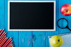 Top view of blank chalkboard and empty textbook apple magnifier pencils and paper clips on blue wooden. Background stock images