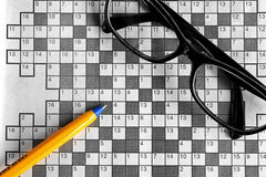 Top view of blank crossword puzzle with eyeglasses and a p Royalty Free Stock Image