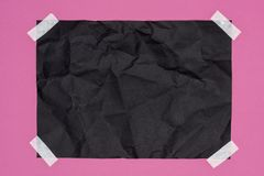 Top view of blank crumpled black paper. On pink stock photography