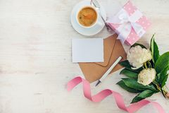 Top view of blank note, kraft envelope, coffee cup and peony flowers over white wood rustic background.Copy space. Royalty Free Stock Image