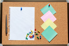 Top view of blank notebook on cork board with pen, note and colo Royalty Free Stock Photography