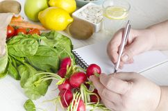 Woman writing her meal and diet plan. Fresh fruits, vegetable and seeds for healthy lifestyle and eating royalty free stock images
