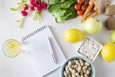 Top view of blank notebook and different fruits, vegetables, nuts and seeds. Concept of balanced diet royalty free stock photography