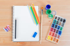 Top view of blank notebook or notepad and watercolour, pencils supplies on the wood background desk.  stock photos