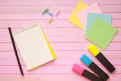 Top view of blank notebook page on pastel colored background office desk with different objects. Minimal flat lay style Royalty Free Stock Image