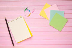 Top view of blank notebook page on pastel colored background office desk with different objects. Minimal flat lay style Stock Image