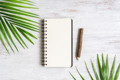 Top view of blank notebook with palm leaf and wooden pencil on grunge white wood background, flat lay with copy space for your. Text. Background for summer royalty free stock image