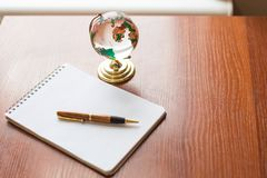 Top view of Blank notebook white paper and globe world map on wooden background with space for your message royalty free stock photo
