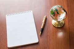 Top view of Blank notebook white paper and globe world map on wooden background with space for your message stock photo