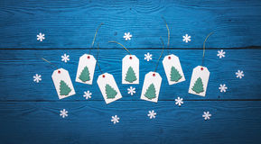 Top view of blank paper tags with Christmas trees. On blue boards Stock Photography