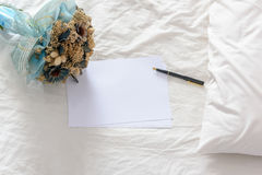 Top view of blank papers with a fountain pen decorated with a bouquet of dried flowers on an unmade / untidy bed. Stock Photography