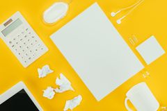 Top view of blank sheet of paper, crumpled papers, notes, calculator, earphones, computer mouse and digital tablet. Isolated on yellow stock images