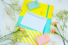 Blank white envelope, gift boxes ,bright folder and flowers on a marble table. Top view blank white envelope, gift boxes ,bright folder and flowers on a marble royalty free stock photography