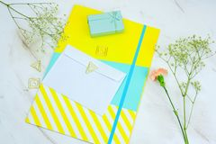 Blank white envelope, gift boxes ,bright folder and flowers on a marble table. Top view blank white envelope, gift boxes ,bright folder and flowers on a marble royalty free stock photos