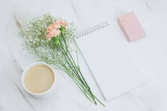 Blank white notebook,coffee cup,gift box and boquet of carnation and gypsophila flowers on a marble background. Top view blank white notebook,coffee cup,gift box stock photography