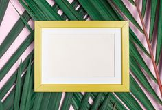 Top view blank yellow photo frame on green palm leaf on pastel p. Ink table top background.Summer vacation backdrop.Mock up for display design and text royalty free stock images