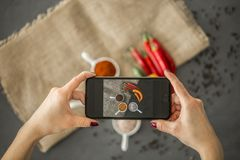Top view of a blogger taking a photo of spices in stylish ceramic dishes for her culinary blog with a smartphone royalty free stock images