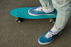 Penny skateboard commute hipster transport solutions. Top view of the blue canvas shoe standing on the blue plastic penny board outdoors. Concept of the modern Stock Photo
