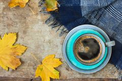 Top view of a blue cup of coffee, blue scarf and golden leaves on wooden background royalty free stock images