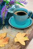 Top view of a blue cup of coffee, purple flowers in a vase and golden leaves on wooden background royalty free stock photography