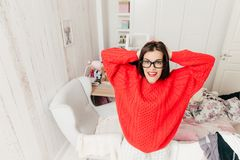 Top view of blue eyed, brunette young female in casual red sweat stock photography
