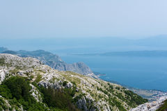 Top view on blue fogged sea bay from the mountain cliffs of Biokovo national park near Makarska resort. Top view on blue fogged sea bay from the mountain cliffs Royalty Free Stock Image