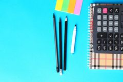 Top view of blue office desk with pencils, calculator and notebook. Back to school concept stock photo