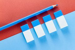 Top view of blue pencil and erasers on  color papers. Top view of a blue pencil and blue and white erasers on blue and brown color papers background Royalty Free Stock Photos