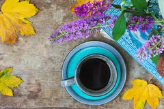 Top view of a blue cup of coffee, book, cookies, purple flowers in a vase and golden leaves on wooden background royalty free stock photography
