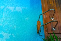 Top view of blue water in swimming pool with grab bars ladder surrounded with wooden floor and green trees. stock image