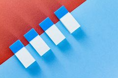 Top view of colorful erasers on  color papers placed diagonally. Top view of blue and white erasers on blue and brown color papers background arranged diagonally Royalty Free Stock Image